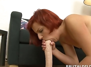 Redhead rotates between brashness and pussy with huge dildo